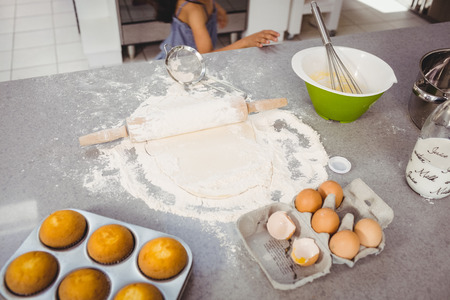 wire mess: High angle view of rolling pin on dough with muffins and egg at kitchen table