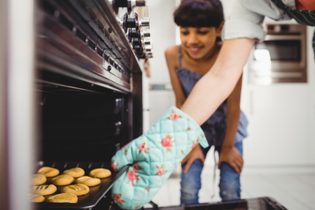 by placing: Cropped hand of woman placing cookies in oven while daughter standing in background Stock Photo