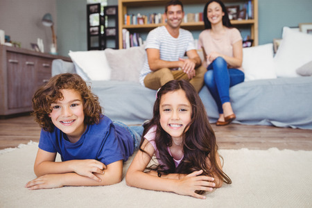 spare time: Portrait of happy siblings lying on carpet against parents siting on sofa