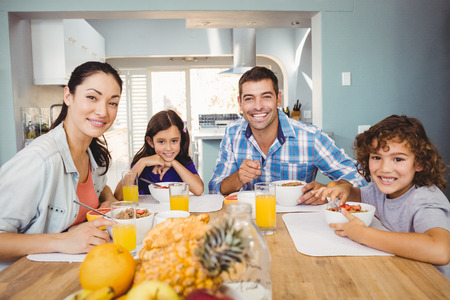 Portrait of happy family having breakfast at home