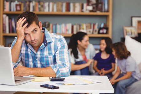 unsmiling: Portrait of tensed man by laptop table while family sitting in background