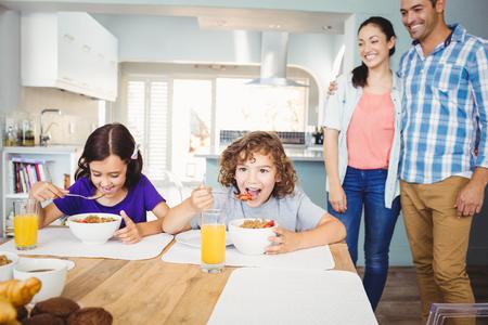 mujeres y niños: Los niños que desayunan mientras que los padres felices de pie junto a la mesa en casa Foto de archivo