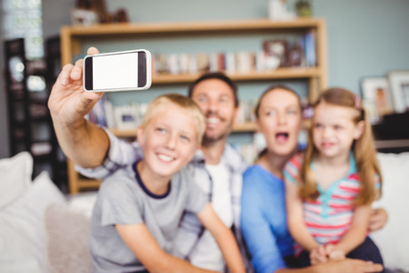 family sofa: Man taking selfie of family with mobile phone while sitting on sofa at home Stock Photo