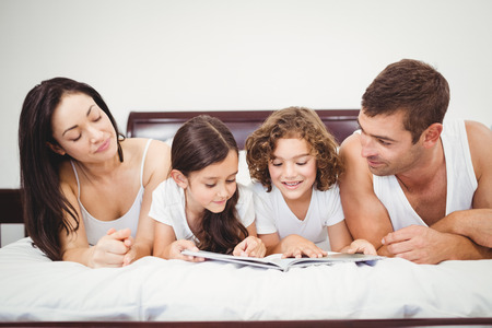 Close-up of children reading book with parents on bed at home