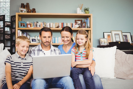 family sofa: Happy family using laptop while sitting on sofa at home
