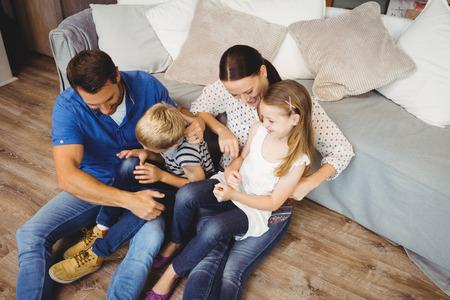 convivencia familiar: Opinión de alto ángulo de la familia feliz que se sienta por el sofá en el salón