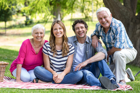 Smiling family sitting on a blanket in the garden