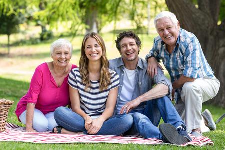 Sourire famille assis sur une couverture dans le jardin