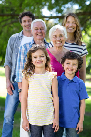 tree line: Smiling family standing in a row in the garden