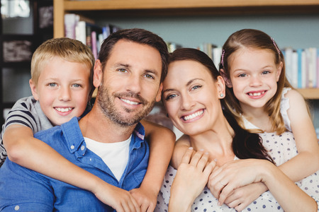 family  room: Close-up portrait of cheerful family against shelf in living room
