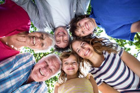 circulo de personas: Familia sonriente con sus cabezas en un círculo en el jardín