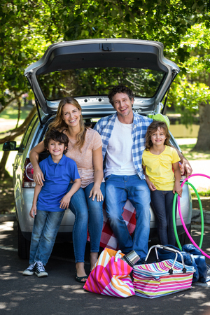 Smiling family sitting in the luggage space of a car Stock Photo