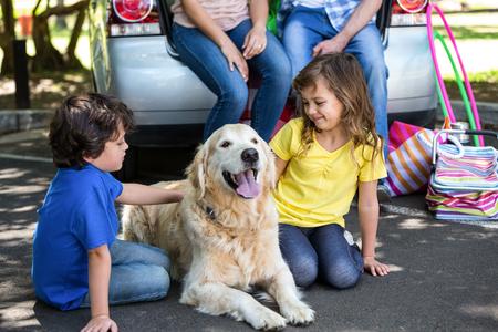 Children ruffling the dogs fur in a park