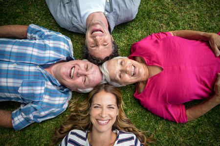 father in law: Smiling family lying in the grass in the garden