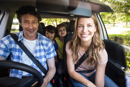 car driving: Smiling family sitting in the car and driving