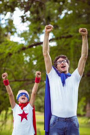 one parent: Father and son dressed as superhero in the garden Stock Photo