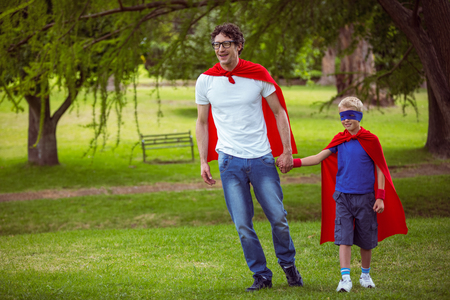 pretending: Father and son pretending to be superhero in park