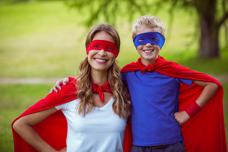 mother to be: Mother and son pretending to be superhero in park Stock Photo