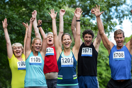 raised arms: Marathon athletes posing with raised arms in park Stock Photo