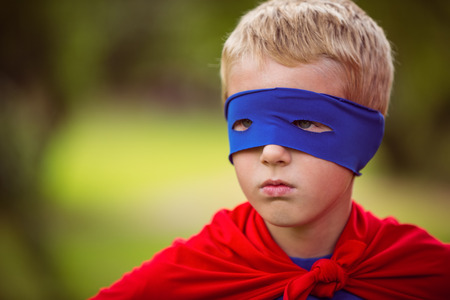 pretending: Little boy pretending to be superhero in park