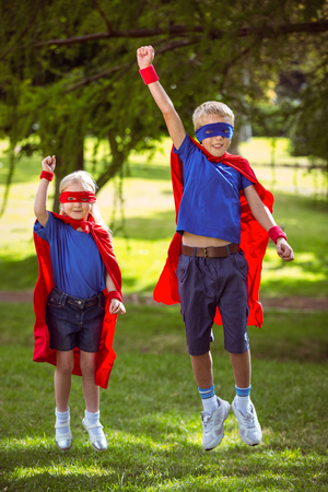 pretending: Brother and sister pretending to be superhero in park Stock Photo