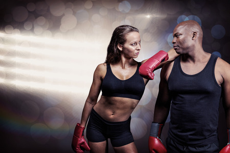 female boxer: Male and female boxer looking at each other against spotlights Stock Photo