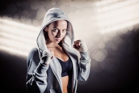fighting stance: Portrait of female boxer in hood with fighting stance against spotlight Stock Photo