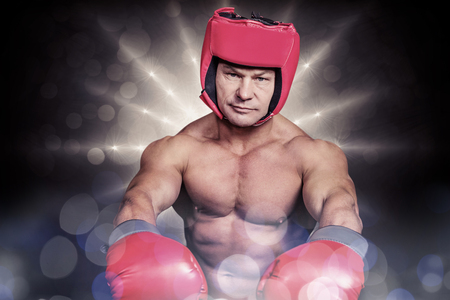 headgear: Portrait of boxer with red gloves and headgear against spotlight