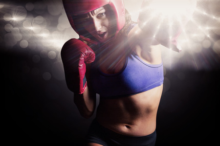 headgear: Female boxer with gloves and headgear punching against spotlight