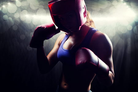 fighting stance: Portrait of female fighter with fighting stance against spotlight Stock Photo