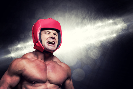 headgear: Angry boxer with headgear against spotlights Stock Photo