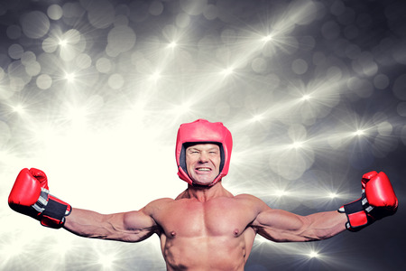 outstretched: Winner boxer with arms outstretched against spotlights