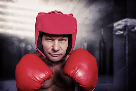 headgear: Portrait of boxer with gloves and headgear against red boxing area with punching bags