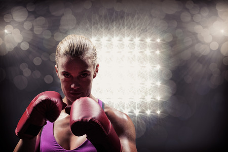 Portrait of woman fighter with gloves against spotlight