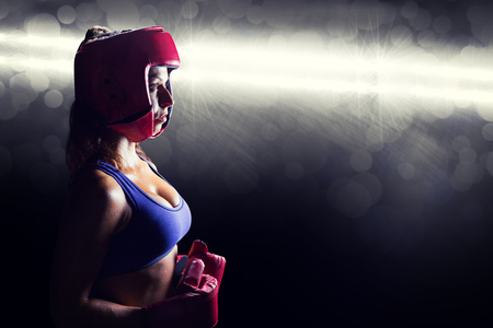 headgear: Side view of female boxer with headgear and gloves against spotlight