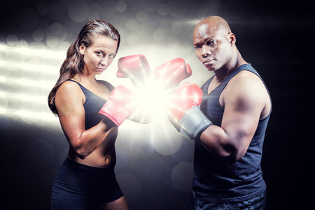fighting stance: Portrait of male and female athletes with fighting stance against spotlight Portrait of male and female athletes with fighting stance against black background