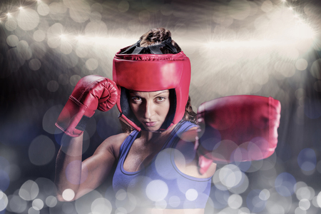 headgear: Portrait of female boxer with gloves and headgear against spotlight
