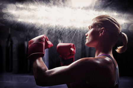 fighting stance: Side view of female boxer with fighting stance against red boxing area with punching bags Stock Photo