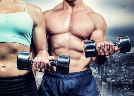 large rock: Midsection of woman and man exercising with dumbbells against large rock overlooking huge city
