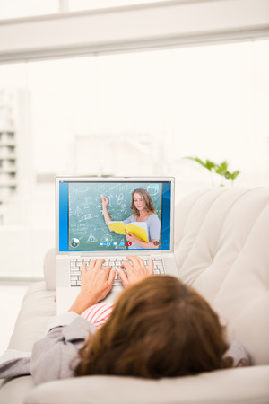 teching: Teacher reading book while writing on blackboard against woman using laptop while relaxing on sofa Stock Photo