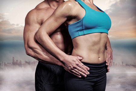 Midsection of healthy couple with hands on hip against cityscape on the horizon Reklamní fotografie