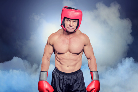 headgear: Portrait of shirtless man with boxing headgear and gloves against cloudy sky