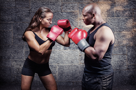 fighting stance: Male and female boxer with fighting stance against grey