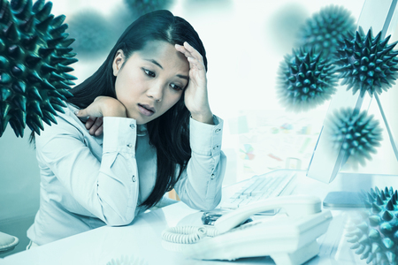 Unsmiling businesswoman with hands on face against view of business stuffs on scale