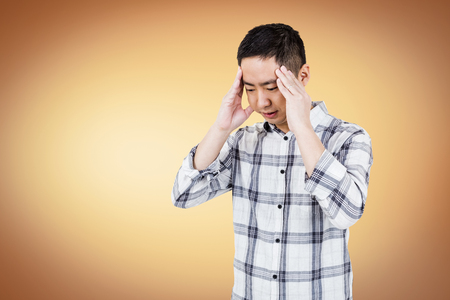 wincing: Asian man getting a headache on white background Stock Photo