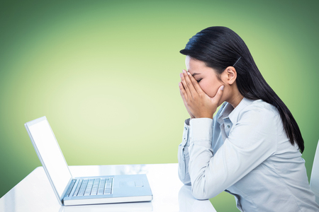 covering the face: Worried businesswoman covering face at the desk in work