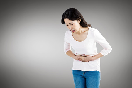unhappiness: Young woman with stomach pain against white screen