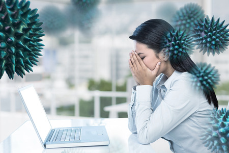 covering the face: Worried businesswoman covering face against office