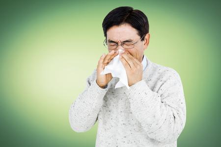 sneezing: Smiling man using a tissue while sneezing