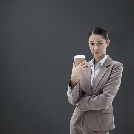 hot secretary: Portrait of a businesswoman holding a takeaway tea against grey background